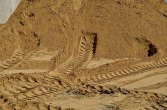 De sporen van de band in het zand stock foto's