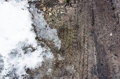 De sporen van de band op het zand De sporen van het wiel op vuil De donkere band volgt achtergrond met sneeuw en water Wielspoor  Stock Fotografie