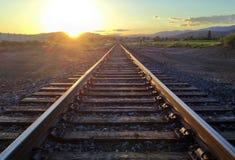 De sporen van de spoorweg bij zonsondergang stock foto