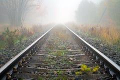 De sporen van de trein in mistig weer Stock Foto's