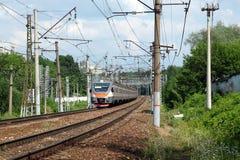 De sporen van het de spoorwegspoor van het stadslandschap en passagierstrein die zich op zonnige de zomerdag bewegen Royalty-vrije Stock Afbeelding