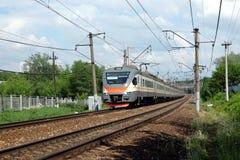 De sporen van het de spoorwegspoor van het stadslandschap en passagierstrein die zich op zonnige de zomerdag bewegen Royalty-vrije Stock Foto