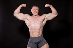 De sport de atletenbodybuilder pronkt met zijn spieren stock afbeelding