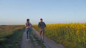 De sporten in openlucht, de jonge sportman en het wijfje met kanekalonvlechten lopen rond op aard op het gazon van de bloesemverk stock videobeelden