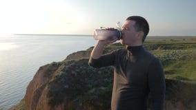 De sportenlevensstijl, fitness wijfje geeft sportmanschudbeker met het drinken van mineraalwater na cardiotraining in helder stock video