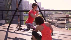 De sportenvrouw is bezet met de trainer op een terassa van sportclub Individuele opleiding vóór competities stock video