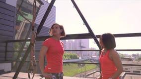 De sportenvrouw is bezet met de trainer op een terassa van sportclub Individuele opleiding vóór competities E stock video