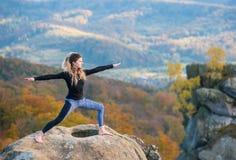 De sportieve geschikte vrouw oefent yoga op de bovenkant van de berg uit royalty-vrije stock foto