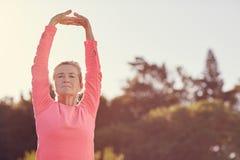 De sportieve hogere vrouw die oefeningsopwarming doen rekt zich in openlucht uit stock foto