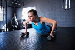 De sportieve jonge domoren van de vrouwenholding in gymnastiek Royalty-vrije Stock Foto