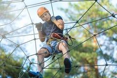 De sportieve, jonge, leuke jongen in witte t-shirt brengt zijn tijd in het park van de avonturenkabel in helm en veilig materiaal stock afbeelding