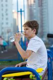 De sportieve leuke jongen drinkt water na het spelen van basketbal op de sportengrond Gezonde Levensstijl royalty-vrije stock foto
