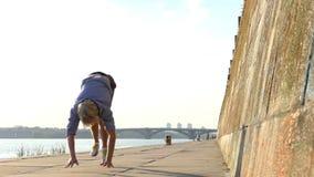 De sportieve Mens danst Disco op een Riverbank met een Hoge Steenmuur in slo-Mo stock video
