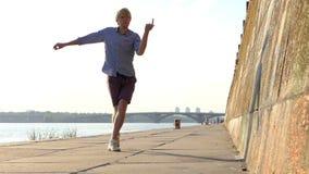 De sportieve Mens danst Disco op een Riverbank met een Steenmuur in de Zomer in slo-Mo stock video