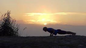 De sportieve mens doet omhoog een duw op een meerbank bij zonsondergang in slo-mo stock footage