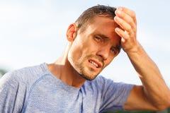 De sportieve mensenclose-up veegt voorhoofd met zijn palm af Stock Fotografie