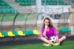 De sportieve sexy vrouw houdt voetbalbal tussen benen royalty-vrije stock afbeelding