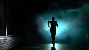 De sportieve vrouw begint in silhouet en rook, vooraanzicht, langzame motie te lopen stock video