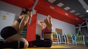 De sportieve vrouw die abs doen oefent uit om vlakke buik te hebben, opleidend in geschiktheidsclub Sporten mooie vrouwen in de g stock video