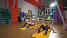 De sportieve vrouw die abs doen oefent uit om vlakke buik te hebben, opleidend in geschiktheidsclub Sporten mooie vrouwen in de g stock footage