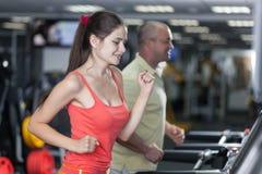 De sportieve vrouw en de man stoten tredmolen aan Stock Foto
