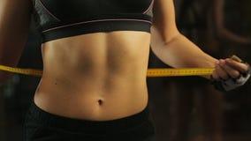 De sportieve vrouw met vlakke buik die haar taille, het verlies van het controlesgewicht meten vloeit voort stock video