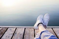 De sportieve vrouw rekte omhoog haar voeten op een houten pier uit royalty-vrije stock foto