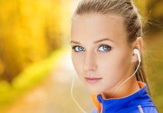 De sportieve vrouwenagent luistert aan muziek in aard Stock Foto's