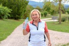 De sportieve zwetende grootmoeder drinkt water royalty-vrije stock foto