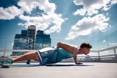 De sportman doet opdrukoefeningen op hoog terras stock fotografie