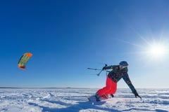 De sportman op een snowboard stelt vlieger in werking Stock Foto