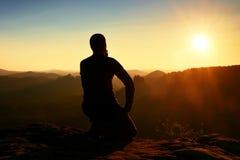 De sportmanwandelaar in zwarte sportkleding zit op bergbovenkant en neemt neer een rust Toeristenhorloge aan ochtend nevelige val Stock Afbeeldingen