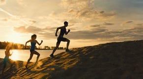 De sportmotivatie - groep atleten - twee meisjes en een kerel vlucht de berg, dichtbij rivier bij schemer royalty-vrije stock afbeelding