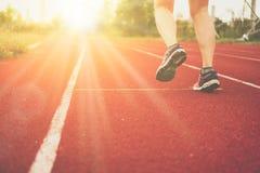 De sportschoen van de vrouwenslijtage in het runnen van hofachtergrond te lopen stock afbeelding