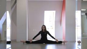 De sporttrainer toont flexibiliteit van haar lichaam aan die oefeningen doen stock videobeelden