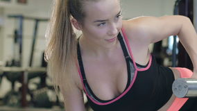 De sportvrouw die opheffende domoren uitwerken stelt binnen bij de gymnastiek langzaam stock videobeelden