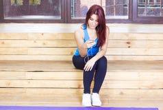 De sportvrouw luistert aan muziek Sport en fitness concept stock afbeelding
