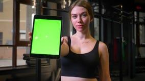 De sportvrouw met paardestaart toont tablet met het chromakey groene scherm in camera die kalm en positief in gymnastiek zijn, stock video