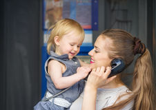 De sprekende telefoon van de moeder en van de baby in stad Stock Afbeeldingen