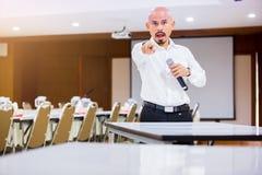 De spreker hield de microfoon in zijn hand en toont zijn wijsvinger aan de luisteraar met onscherpe conferentieruimte en projecto royalty-vrije stock foto