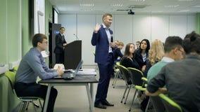 De spreker spreekt aan studenten bij een lezing op economie Mannelijke handgebaren en vertoningen het beeld van de projector stock videobeelden