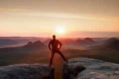 De springende wandelaar in zwarte viert triomf tussen twee rotsachtige pieken Prachtige dageraad met zon boven hoofd Stock Foto