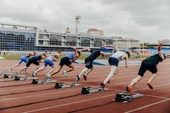 De sprinters van beginmensen op 100 meters het lopen Stock Afbeelding