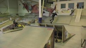De sprong die van de rolschaatser zich drie keer in lucht omkeren springplank ontbreek Concurrentie in skatepark stock videobeelden