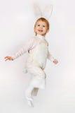 De sprong n van het gelukmeisje een wit donsachtig konijntjeskostuum stock fotografie
