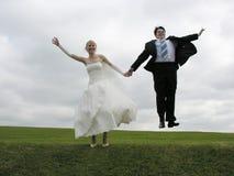 De sprong van de bruid en van de bruidegom Stock Foto