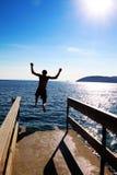 De sprong van de jongen aan water stock foto's