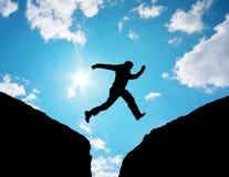 De sprong van de mens door het hiaat. Stock Afbeelding