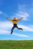 De sprong van de mens op de groene weide stock fotografie