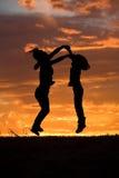 De sprong van de moeder en van de dochter bij zonsondergang. Stock Fotografie
